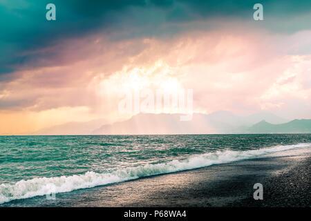 Schönen Sommer Marine mit Bergen Silhouette. Bewölkt rosa Himmel mit Sonnenstrahlen durch die Wolken. Strand von Salerno, Italien - Stockfoto