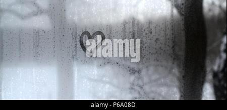 Das Herz ist auf der beschlagenen Glas im Winter gemalt. - Stockfoto