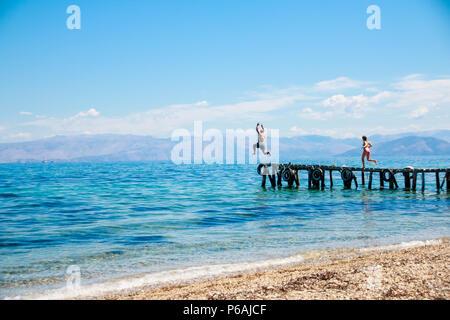 Jugendliche springen die Pier ins Meer. fun Sommerferien. Junge Mann springt in den blauen Wasser aus Pier. Blick in Bewegung. Glück, Sommer, Spass. Kopieren Sie Platz - Stockfoto