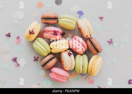 Lecker Pink, Gelb, Grün und Braun makronen am trendigen Pastellfarben grauem Papier mit lila Blumen und Konfetti. Platz für Text. leckere bunte Makronen - Stockfoto