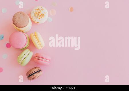 Moderne Nahrungsmittel fotografie Konzept. Stilvolle bunte Makronen am trendigen rosa Papier, flach. Platz für Text. Lecker rosa, gelb, grün, weiß, braun Mac - Stockfoto