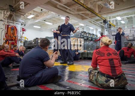 160830-N-TH 560-049 PAZIFISCHEN OZEAN (Aug. 30, 2016) Leutnant Lukas Dundon, Assistant Befehl Kaplan an Amphibious Assault ship USS BONHOMME RICHARD (LHD 6), spricht mit Waffen Abteilung Seeleute während einer interaktiven Selbstmord Sensibilisierung und Prävention Schulung. Bonhomme Richard, dem Flaggschiff der Bonhomme Richard Expeditionary Strike Group, ist in den USA der 7. Flotte Bereich für Maßnahmen zur Erhöhung der Sicherheit und Stabilität in der Indo-Asia-Pazifik-Region. (U.S. Marine Foto von Mass Communication Specialist 3. Klasse Jeanette Mullinax/Freigegeben) - Stockfoto