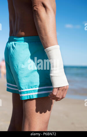 Nahaufnahme eines jungen kaukasischen Mann in Badehose am Strand mit einem Verband in seinem Handgelenk, direkt am Meer. - Stockfoto