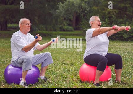Lächelnd senior Sport Frau und Mann sitzt auf Fitness Ball mit Hanteln - Stockfoto