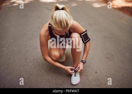 Passen junge blonde Frau in Sportkleidung kniend auf einer Landstraße Musik hören, während Ihr die Schuhe zu binden, bevor sie für einen Stoß - Stockfoto