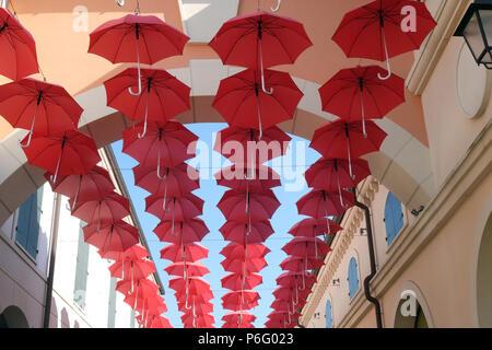 Viele rote Schirme fliegen im Himmel über city street in Venedig, Italien - Stockfoto
