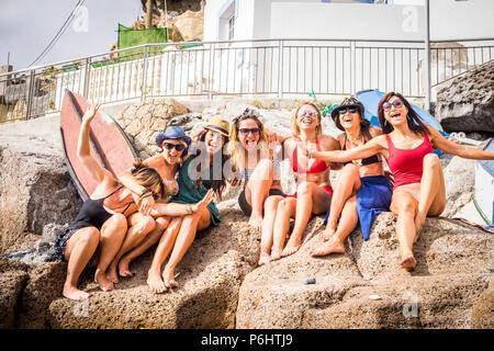 Enjoye Gruppe von netten und schönen Freunde zusammen lächeln Spaß in Freundschaft Sommer Freizeit im Freien in der Nähe des Strandes. squimsuits und Damen - Stockfoto