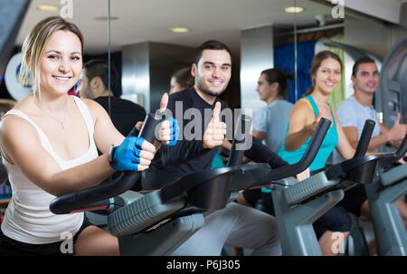 Aktive amerikanische Erwachsene Reiten Fahrräder in Fitness Club - Stockfoto