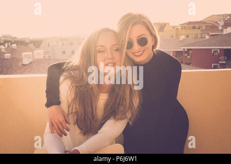 Paar zwei schöne Modelle Frauen umarmen Außenpool auf der Dachterrasse zu Hause. Sonnenuntergang und Sonnenlicht mit Hintergrundbeleuchtung, Eleganz und Schönheit in - Stockfoto
