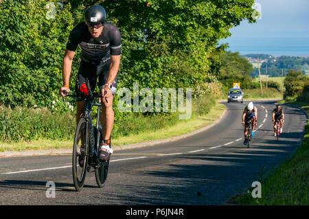 Byres Hill, East Lothian, Schottland, Vereinigtes Königreich, 1. Juli 2018. Edinburgh - Ironman 70.3, Byres Hill, East Lothian, Schottland, Vereinigtes Königreich, 1. Juli 2018. Radfahren Teil der Ausdauer sportliche Veranstaltung. Wettbewerber Radfahren bergauf Vergangenheit Byres Hügel, der auf einem 56 km langen Rundfahrt bike Kurs nach Abschluss der 1,2 Kilometer Schwimmen im Preston Links, durch ein 26,1 Kilometer um Edinburgh als Teil des Triathlon Veranstaltung gefolgt - Stockfoto