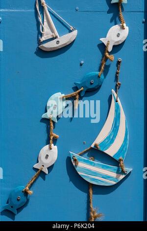Holz- segeln Boote und Meer Fische auf einen String als Dekoration auf einem bunten Hütte Tür. - Stockfoto