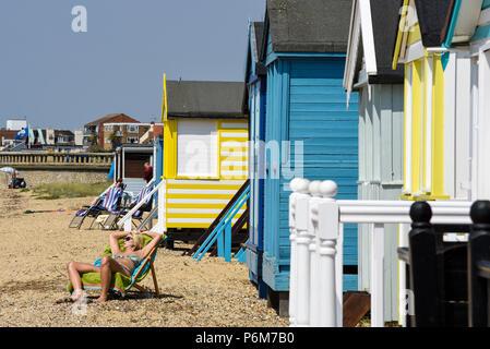Weibliche Sonnenanbeter durch mehrfarbige bunten Holzhütten am Southend On Sea, Essex, Großbritannien - Stockfoto