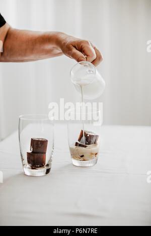 Frau Vorbereitung Eiskaffee. Gefrorenen Kaffee Eiswürfel in ein Glas mit Milch goß einen erfrischenden Sommer trinken zu machen. Weißer Hintergrund. Körperteile. - Stockfoto