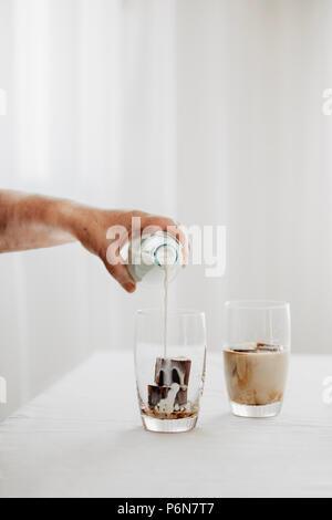 Gefrorenen Kaffee Eiswürfel in ein Glas mit Milch goß einen erfrischenden Sommer Eiskaffee trinken zu machen. Weißer Hintergrund. Körperteile. - Stockfoto