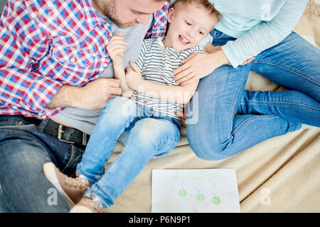 Eltern kitzeln Cute Little Boy - Stockfoto
