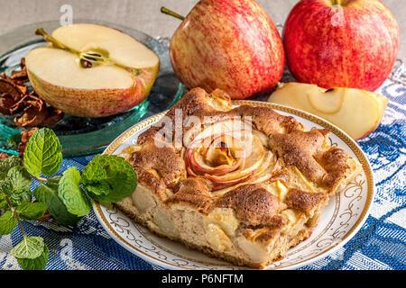 Leckeren warmen Apfelkuchen auf dem Teller mit frischen Äpfeln. Ein Stück des Kuchens mit in Scheiben geschnittenen roten Apfel in der Mitte. Berühmte Tarte mit verschiedenen Arten von Rezepten. - Stockfoto