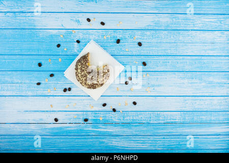 Gebissen Leckere süße Krapfen auf Papier auf Zerkratzt Blau Weiß hohen Kontrast Holz Hintergrund mit ganzen Körnern Oat Meal und Kaffeebohnen auf dem oberen Winkel - Stockfoto