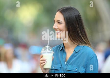 Gerne Frau mit einem Smoothie und das Betrachten der Seite auf der Straße - Stockfoto