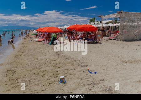 Griechische Mediterranean Beach Bar mit Masse. Die Badegäste, die sich auf Liegen unter roten und weißen Sonnenschirmen an einem sandigen Freizeitaktivitäten Strand auf der Halbinsel Chalkidiki. - Stockfoto