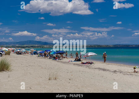 Griechische Strand am Mittelmeer mit Masse. Die Badegäste, die sich auf Liegen unter Sonnenschirmen an einem sandigen Freizeitaktivitäten Beach in Chalkidiki Halbinsel. - Stockfoto