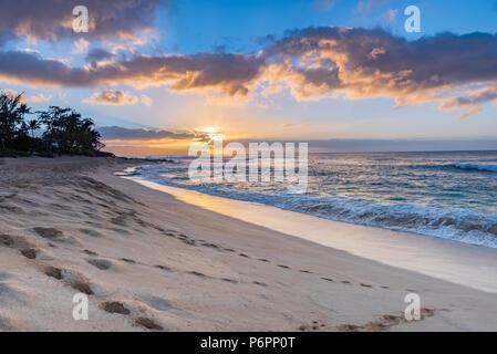 Sonnenuntergang über Sunset Beach auf der North Shore von Oahu, Hawaii mit surf Rollen in über Coral Felsen am Strand - Stockfoto