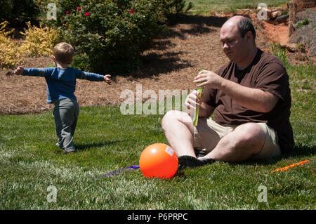Charlotte, NC - 17. April 2016: Vater verwendet eine Bubble Maker Spielzeug, während er draußen sitzt im Gras. Der junge Sohn läuft nach dem Blasen, die floati - Stockfoto