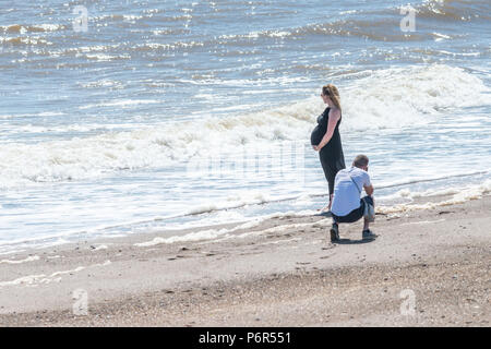 Skegness, Großbritannien. 2. Juli 2018. Ein junges Paar am Strand von Skegness genießen die derzeitige Hitzewelle heißes Wetter und Temperaturen von 30 Grad. Der Mann ist ein Foto von seiner schwangeren Partner, während Sie am Strand mit den Wellen steht zu Ihren Füßen. Credit: Steven Booth/Alamy leben Nachrichten - Stockfoto