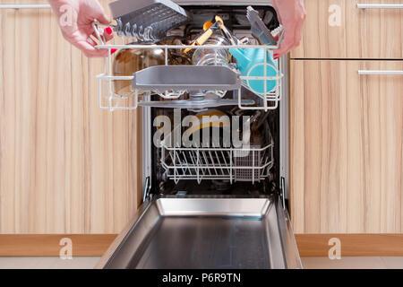 Foto von der Hand des Mädchens Eröffnung Spülmaschine mit schmutzigen Geschirr - Stockfoto