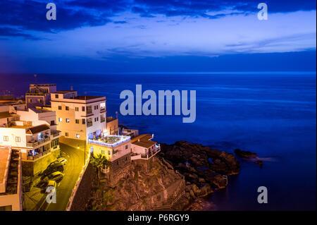 Gebäude auf den Felsen und den Atlantik Nacht Szene. Puerto de Santiago. Islans Teneriffa, Kanaren, Spanien - Stockfoto
