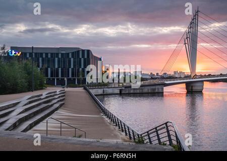Bunte untergehende Sonne über Wasser und Calatrava - style Brücke in einem städtischen Umfeld in Salford Quays, Manchester, UK, mit der Itv Studios - Stockfoto