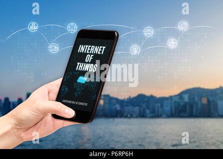 Hand Handy mit Internet der Dinge (Iot) Wort auf dem Bildschirm mit dem Symbol Funktion glühende in Luft mit blur Stadt Gebäude Hintergrund, digitalen Lifestyle. - Stockfoto