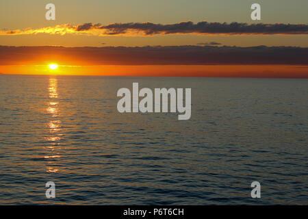 Einen wunderschönen Sonnenaufgang oder Sonnenuntergang über dem Wasser auf den Atlantischen Ozean - Stockfoto