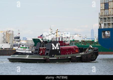 Moran Abschleppen des Traktors tug JRT MORAN eskortieren einen Container schiff entlang der geschäftigen Kill Van Kull Osten in den Hafen von New York. Freedom Tower im Hintergrund. - Stockfoto