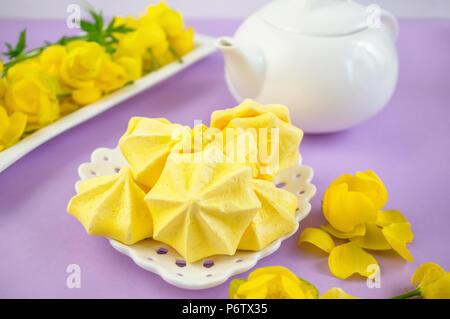 Gelbe meringue auf einem lila Hintergrund in einem Tee mit einem weißen Wasserkocher dienen.