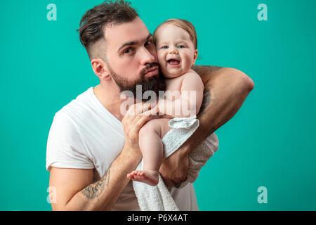 Pflege Mann mittleren Alters zu behandeln sein Kind ein Jahr alten Kind bitte, Spielen und streicheln Sie über blauen Hintergrund isoliert. Glückliche Vaterschaft con - Stockfoto