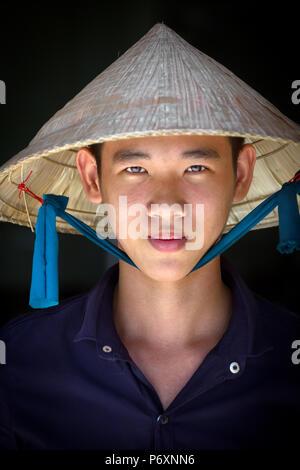 Porträt eines jungen Mannes mit traditionellen konischen Hut in Can Tho, Vietnam