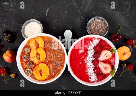 Smoothie Schalen. Gesundes Frühstück Schüssel auf schwarzen Hintergrund. Aprikose Smoothie mit Blackberry und Chia Samen. Himbeer Smoothie mit Erdbeere und Co - Stockfoto