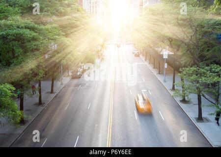 New York City Taxi beschleunigt die 42nd Street in Manhattan mit dem Sonnenuntergang im Hintergrund - Stockfoto