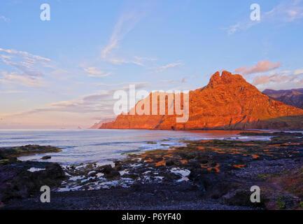 Spanien, Kanarische Inseln, Teneriffa, Punta del Hidalgo, Küste und Anagagebirge während des Sonnenuntergangs. - Stockfoto