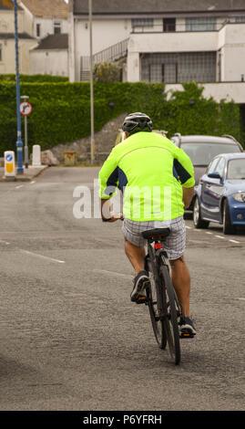 Person Radfahren entlang einer Straße mit einer hellen Jacke - Stockfoto