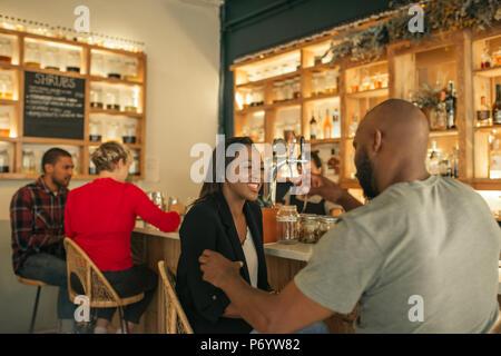 Lächelnd Afrikanische Amerikanische paar Getränke in der Bar genießen. - Stockfoto