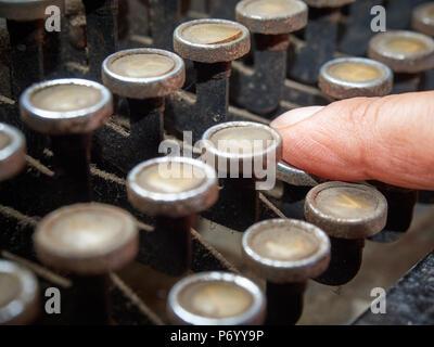 Closeup Finger tippen auf vintage Schreibmaschine mit Staub bedeckt - Stockfoto
