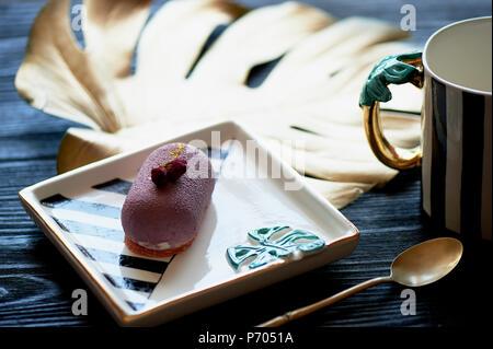 Lila Früchte Mousse Cake, auf einer schönen Untertasse. Auf einem dunklen Hintergrund, mit einem Blatt monstera in gold Lack lackiert. Kulinarische Kunst - Stockfoto