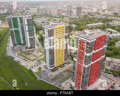 Luftaufnahme von drei hohen Wolkenkratzer von roten, grünen und gelben Farben in kleinen Gebäude mit Parkplatz für Autos und ein Kinderspielplatz in y - Stockfoto