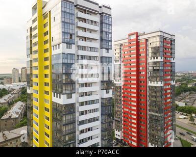Nahaufnahme Luftaufnahme von zwei hohen Wolkenkratzer von roten und gelben Farben in kleinen Gebäude mit Parkplatz für Autos und ein Kinderspielplatz in y - Stockfoto