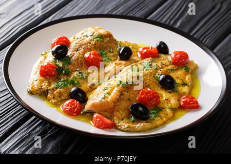 Italienische forellenfilet Fisch mit Knoblauch Zitronensauce, Tomaten, Petersilie und Oliven close-up auf einem Teller auf dem Tisch. Horizontale - Stockfoto