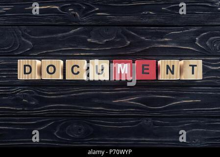 Blick von oben auf die Word Dokument aus Holzklötzen auf dunklen, hölzernen Tischplatte - Stockfoto