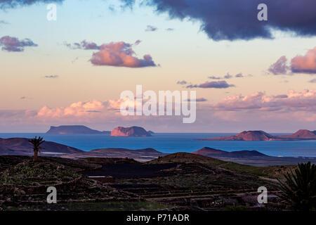 Blaue Stunde erhöhten malerische Landschaft von Lanzarote, hohe Blick auf die anderen Kanarischen Inseln, Spanien, nach Sonnenuntergang mit ausdrucksstarken Himmel voll mit schönen rosa Wolken über dem Atlantik - Stockfoto