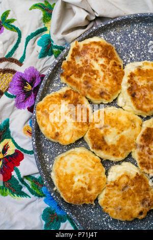 Frisch gebackene Quark Pfannkuchen mit Rosinen in eine Pfanne geben und mit farbigen Blumen Tischdecke bestickt. Ansicht von oben - Stockfoto