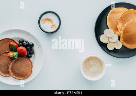 Draufsicht auf das köstliche Frühstück für Zwei mit Pfannkuchen und Kaffee am weißen Tisch - Stockfoto